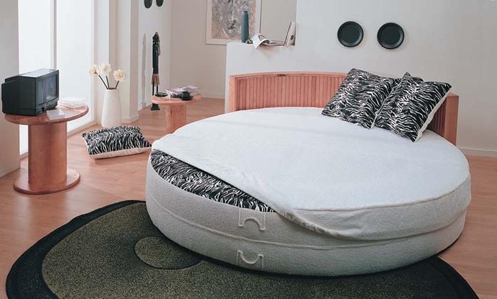 Круглая кровать создает неповторимый интерьер спальни, благодаря своей.