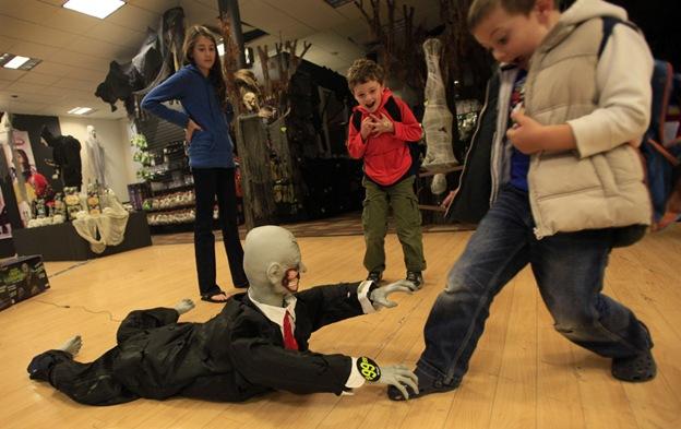 Дети играют с хэллоуинским манекеном в магазине «Дух Хэллоуина» 13 октября в Нью-Йорке