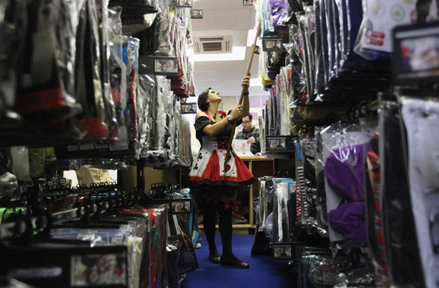 Работница магазина «Angels Costumiers» ищет на складе костюм для клиента 29 октября в Лондоне