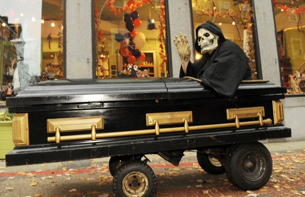Фрэнк Мэйджор из Чикопи, штат Массачусетс, в костюме Смерти едет в гробу на колесиках 27 октября в Салеме, штат Массачусетс