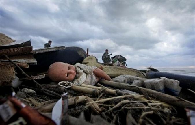 Пластиковая кукла лежит среди другого мусора собранного с моря солдатами и другими сотрудниками чрезвычайных ситуаций, после эфиопской аварии самолета на пляже Хальде к югу от Бейрута, Ливан, 25 Январь 2010.