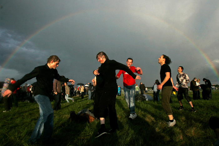 People dance under the rainbow as they refuse to let the wet weather dampen their high spirits during the Bela Music 2009 rock festival at the Borovaya airfield just outside of the Belarus capital Minsk, Saturday, May 23, 2009.(AP Photo)