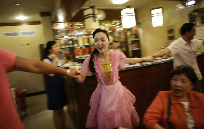 A North Korean waitress dances with Chinese visitors at a North Korean restaurant in the Chinese border city of Dandong, May 28, 2009. (REUTERS/Jason Lee)