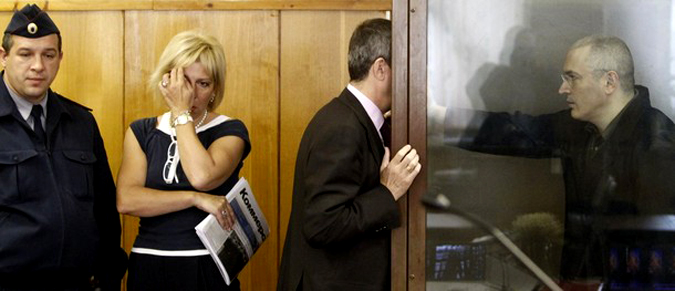 Заключенный в тюрьму бывший нефтяной магнат Михаил Ходорковский (справа) разговаривает со своим адвокатом, который стоит  рядом с неизвестной женщиной во время судебного заседания в Москве, 18 мая 2010 года.