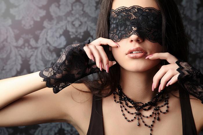 Фото Девушка в черной маске на глазах и в перчатках.