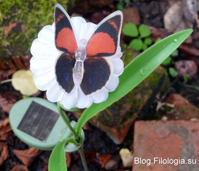 Игрушечная бабочка на цветке