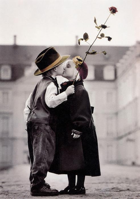 Мальчик и девочка целуются.