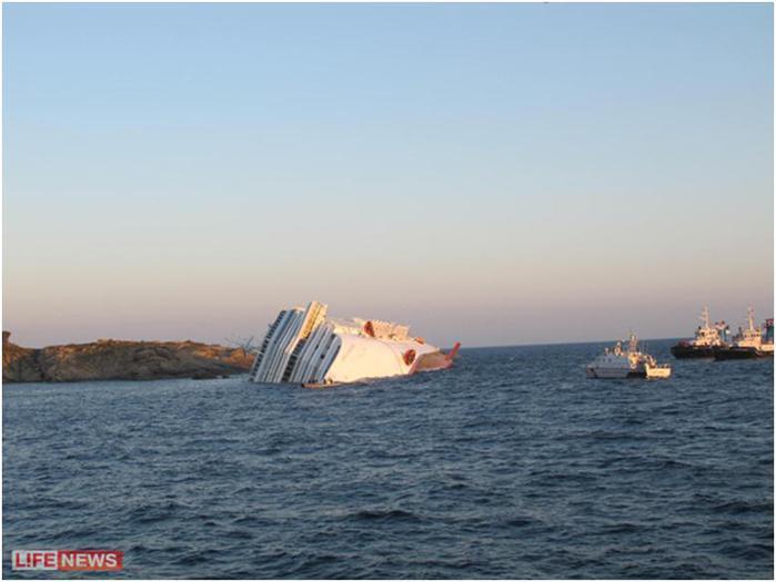 Буксиры, подоспевшие на помощь на фоне громадины корабля казались игрушечными