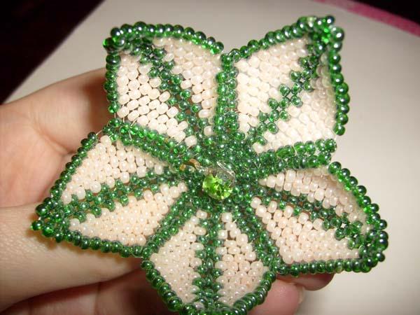 9. Для сердцевинки возьмите крупную бусину, оплетите ее бисером и закрепите в центре цветка.
