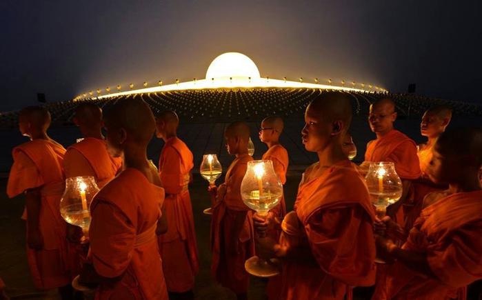 Буддийские монахи шествуют со свечами вокруг пагоды во время празднования Макха Бучи возле дхаммакайского храма в провинции Патхумтхани, Таиланд (700x435, 283Kb)