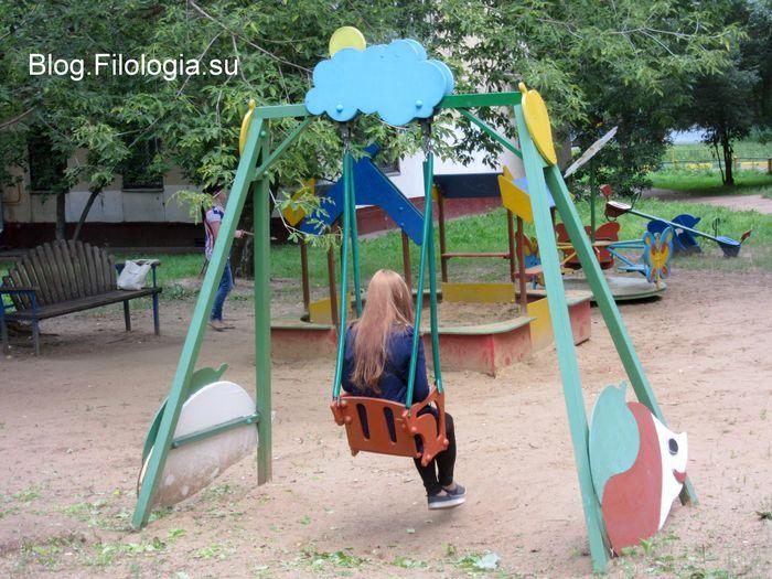 Девушка сидящая на качелях на детской площадке (700x525, 87Kb)