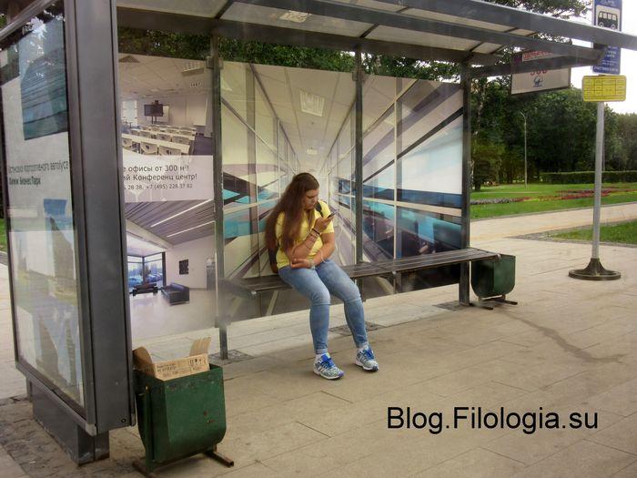 Девушка с телефоном сидящая на автобусной остановке (700x525, 64Kb)