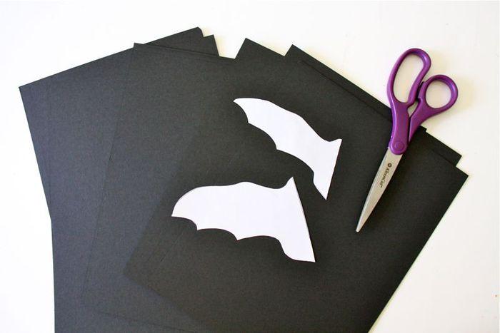 Приложите выкройку к сложенному пополам листу черной бумаги и вырежьте летучую мышь.