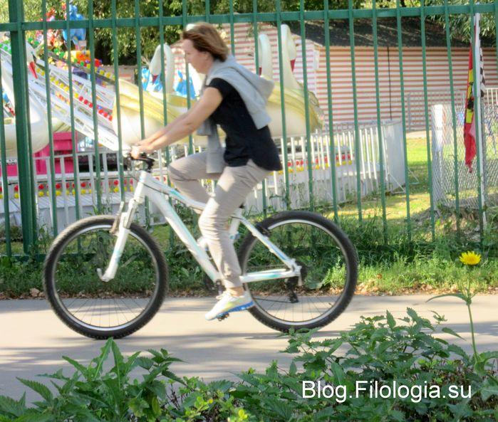 Молодая женщина едет на велосипеде по дорожке парка(699x593, 99Kb)