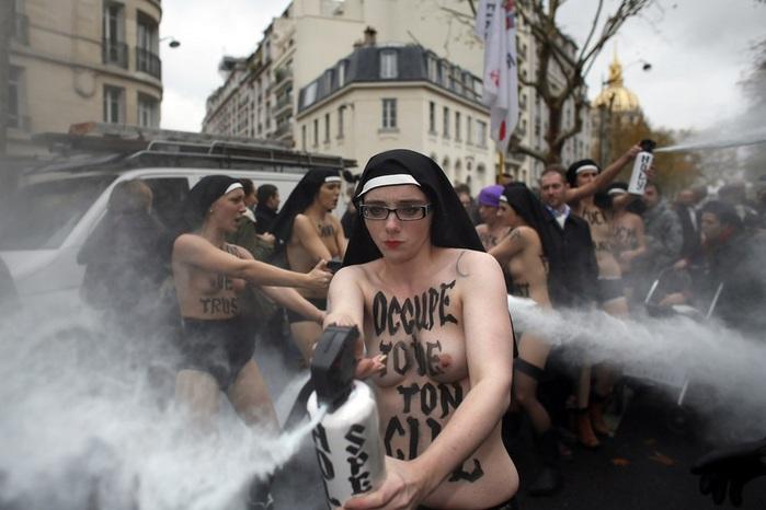 обнаженные активистки FEMEN распыляют жидкость, Париж, Франция. (KENZO TRIBOUILLARD AFP Getty Images) (700x466, 87Kb)
