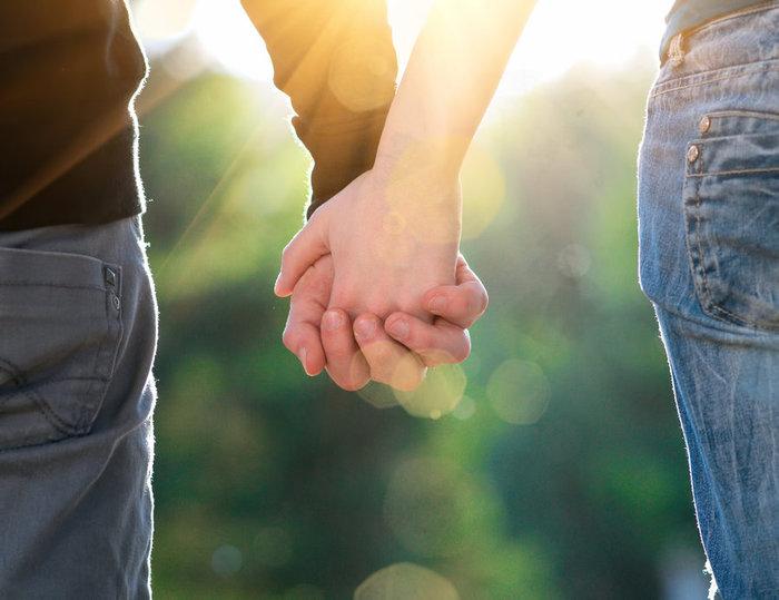Концепция стрелять дружбы и любви мужчины и женщины: две руки над sun ray и