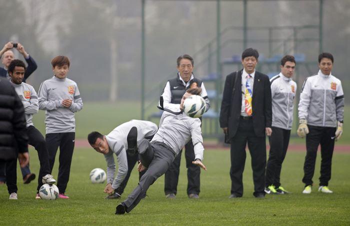 Дэвид Бекхэм упал в костюме и галстуке на футбольном поле. Фотографии