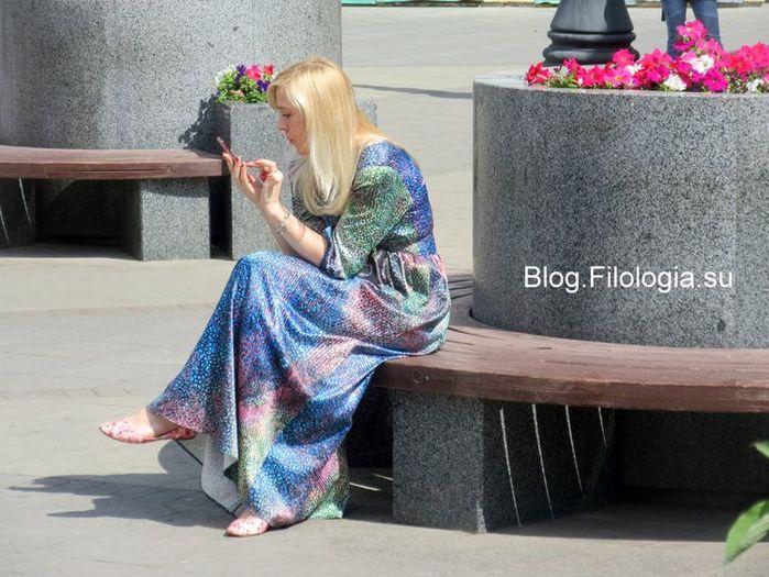 Сидящая девушка с телефоном у метро