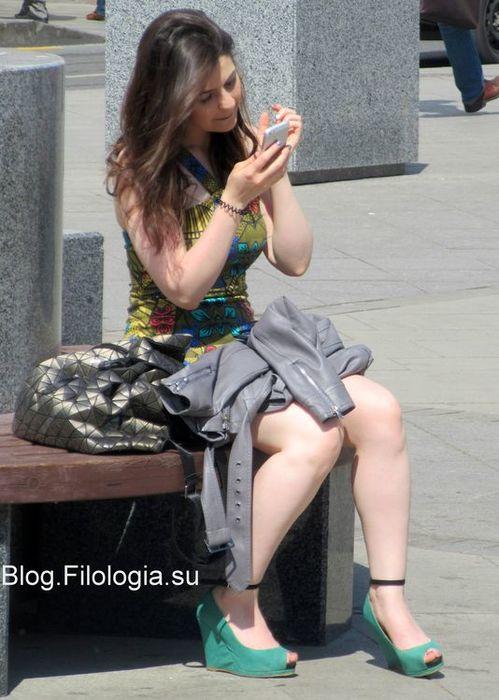 Сидящая на скамейке  девушка, занятая своим мобильным телефоном