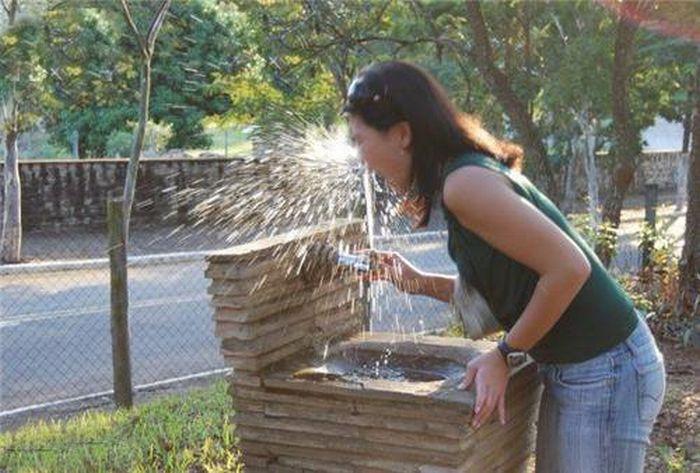 Струя уличного фонтанчика бьет девушке в лицо