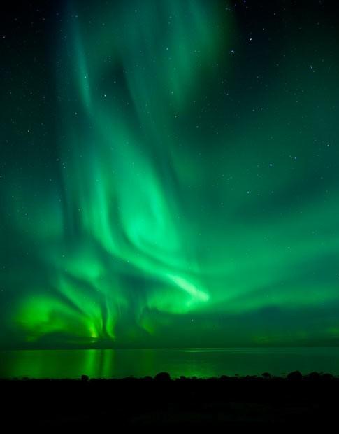 Мощная вспышка сияния над открытым морем в Eggum на Лофотенских островах в Норвегии. Северное сияние (Aurora Borealis) заснятое Бьорном Йоргенсеном (Bjorn Jorgensen) в Норвегии.