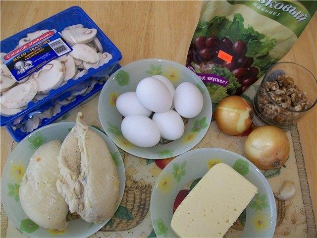 Куриные грудки отвариваем до готовности, слегка подсаливаем Яйца трем на крупной терке. Два белка оставляем для украшения. Сыр и чеснок также трем на терке и смешиваем друг с другом. Лук мелко режем и жарим вместе с грибами в растительном масле. Орехи изм
