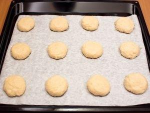 Из теста сформировать небольшие лепешечки (если Вы хотите, чтобы печенье было плоским, лепешечки должны быть тонкими). Противень застелить бумагой для выпечки (или немного смазать маслом). Выложить лепешечки.