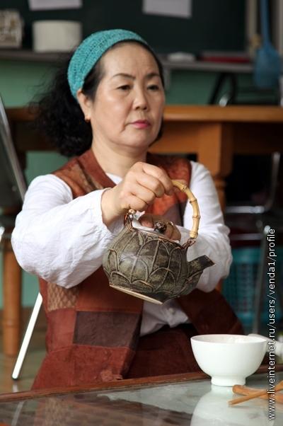 Из чайника наливают кипяток в чашу. Движения медленные, плавные, струя должна журчать. Очень важно придерживать крышку салфеткой в левой руке.