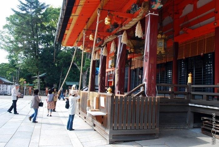 Огромный действующий буддийский храм. Верующие подходят, бросают монетку, молятся, сложив руки и бьют в гонг.