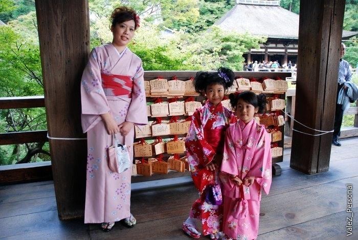 И снова три японки в кимоно, на фоне табличек с желаниями. Покупаешь табличку, вешаешь и она висит в храме