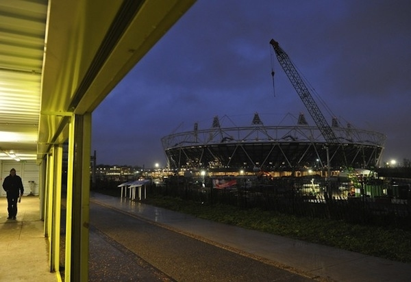 A man walks near the Olympic Stadium at the London Olympic site in Stratford, in east London, November 18, 2010. REUTERS/Toby Melville (BRITAIN - Tags: BUSINESS CONSTRUCTION SPORT OLYMPICS)