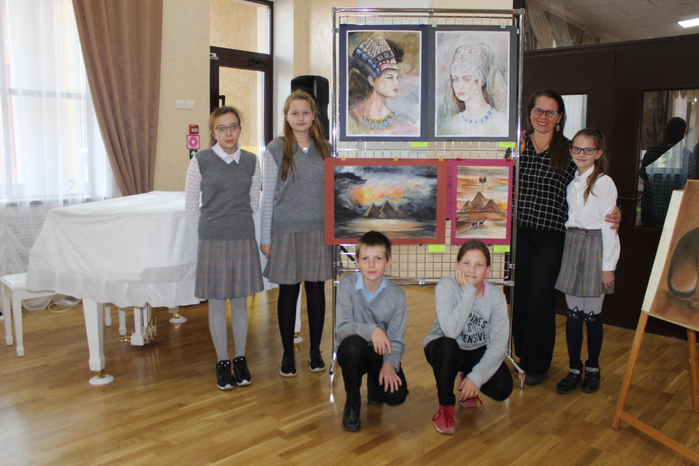 Учащиеся школы искусств на фоне своих работ